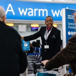 British Airways employee assists passengers with check-in