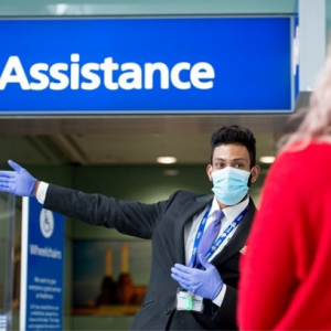A man wearing face masks and gloves at Heathrow airport offering passenger assitance